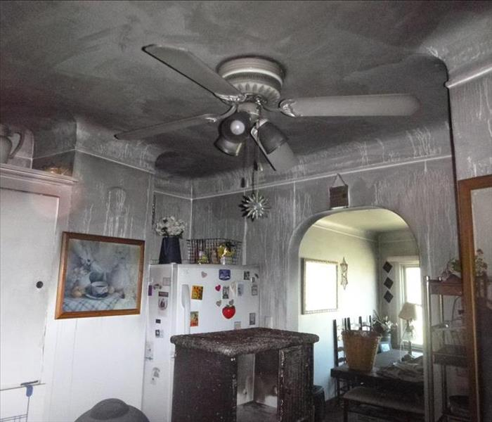 white walls covered in black soot in kitchen